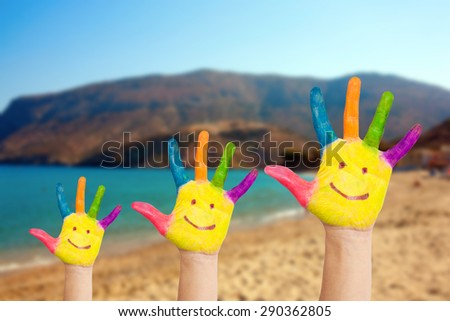 Smiley on family hands against beach and blue sea background. Summer vacation and family freedom concept with copy space - stock photo