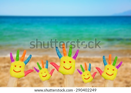 Smiley on hands against beach, sand, sea and sky background. Summer vacation and family freedom concept with copy space - stock photo