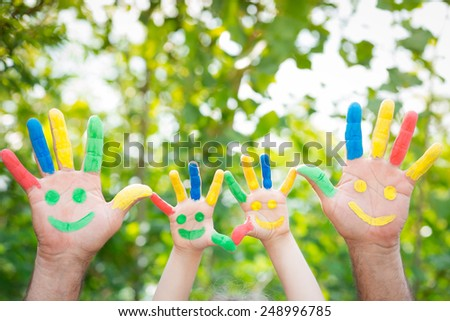 Smiley on hands against green spring background. Family having fun outdoors - stock photo