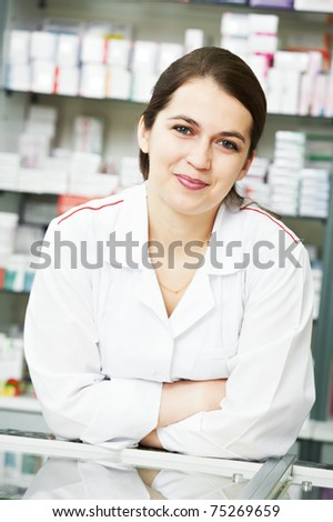 smiley pharmacist chemist woman standing in pharmacy drugstore - stock photo