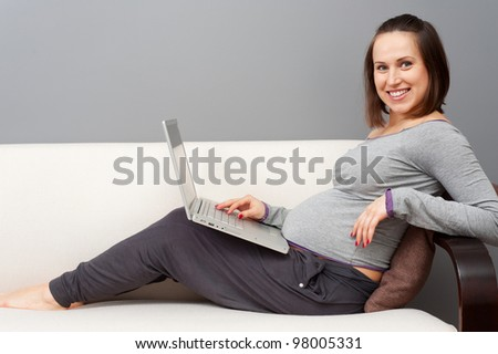 smiley pregnant woman with laptop at home - stock photo