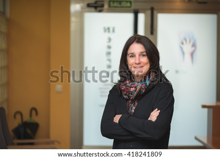 smiley professional entrepreneur middle aged brunette woman at entrance hall workplace standing and crossing arms - stock photo