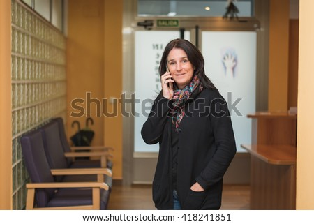 smiley professional entrepreneur middle aged brunette woman at entrance hall workplace standing and talking on phone