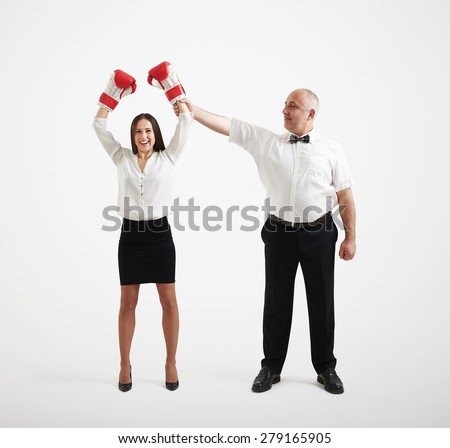smiley referee holding happy winner businesswoman in boxer gloves and looking at her, isolated on light grey background - stock photo