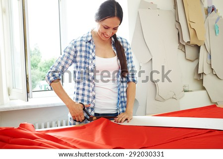 smiley seamstress working with  pattern and red textile - stock photo