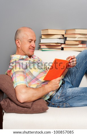 smiley senior man reading the book at home