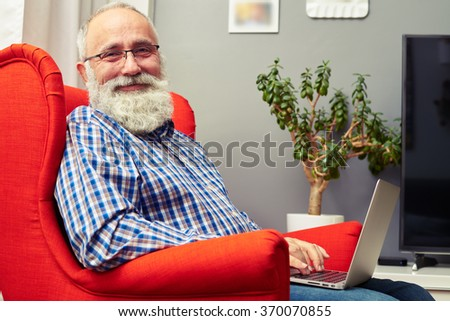 smiley senior man working with laptop and looking at camera - stock photo