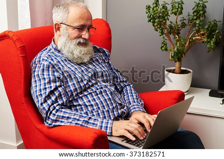 smiley senior man working with laptop at home
