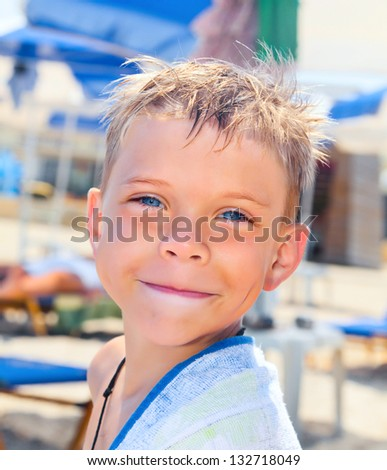Smiley seven years old boy on the beach with towel - stock photo