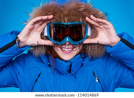 smiley skier looking through mask. studio shot over blue background