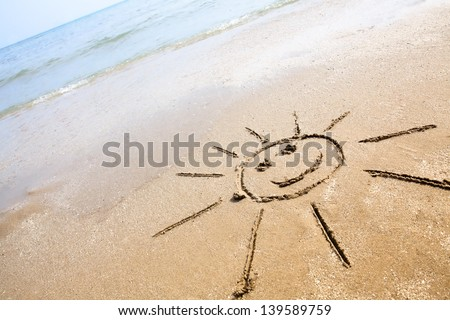 Smiley sun drawing on the sand beach. Perfect for greeting cards, positive and happiness concept. - stock photo