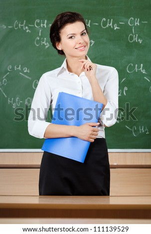 Smiley teacher at the blackboard holds 	blue writing pad