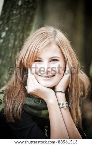 Smiley Teenager with long brunette hair and braces - stock photo
