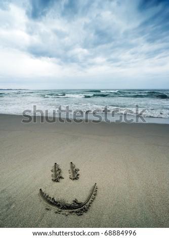 Smiley texture on beach - stock photo