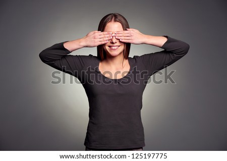 smiley woman covering her eyes by hands over dark background - stock photo
