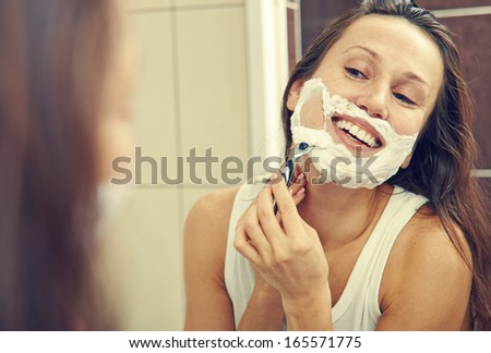 smiley woman looking at mirror and shaving her face  - stock photo