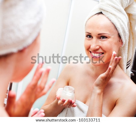 smiley woman looking in mirror and applying cream