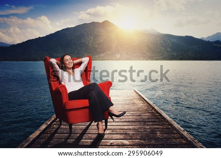 smiley woman resting and dreaming on the red chair on wood moorage over beautiful landscape  - stock photo