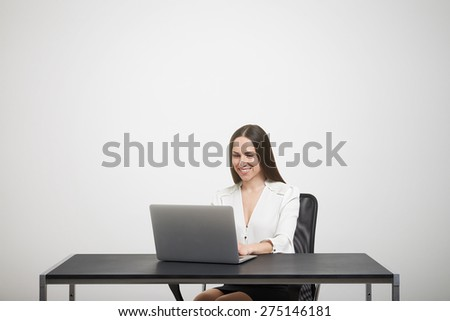 smiley woman sitting at the table with laptop, typing on keyboard and looking at screen over light grey background with empty copyspace overhead - stock photo