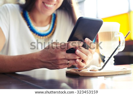 smiley woman using smartphone in cafe. focus on the hand - stock photo