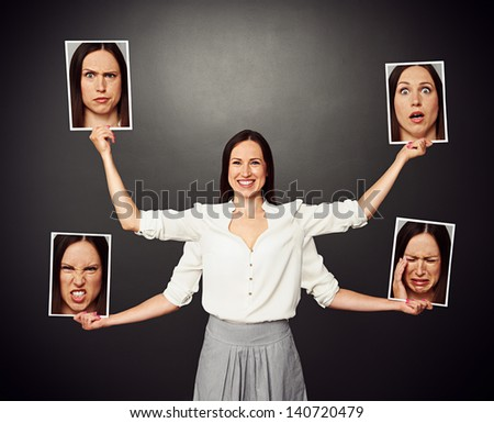 smiley woman with four hands holding pictures with different emotional faces - stock photo