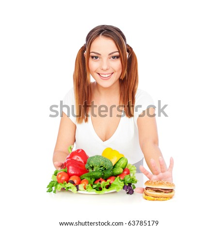 smiley woman with vegetables and burger. isolated on white - stock photo
