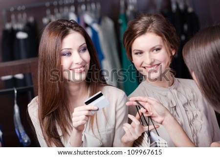Smiley women pay with credit card for purchases - stock photo
