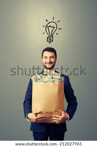 smiley young businessman with drawing light bulb above the head holding paper bag with money. photo over grey background - stock photo