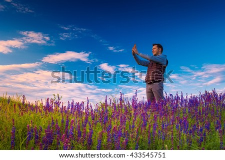 Smiley young man, standing on a green grass field with wild flowers, taking picture on phone against blue sky. - stock photo