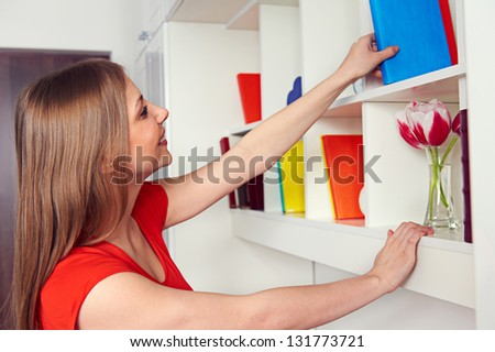 smiley young woman getting book from the shelf - stock photo