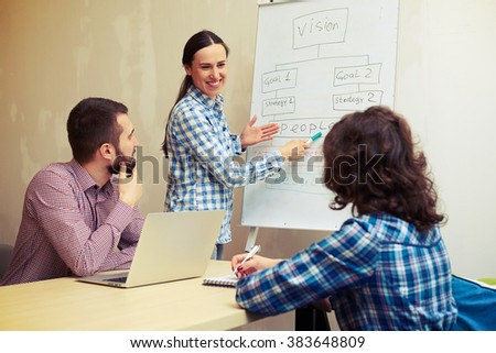 smiley young woman standing near white board, pointing and looking at her colleagues - stock photo
