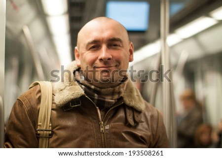Smilinf man holding  handrail on  subway - stock photo