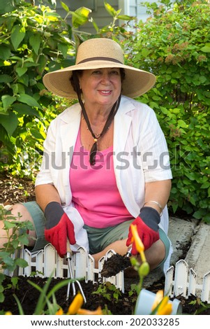 Smiling active elderly lady tending flowerbeds around the house sitting in her wide brimmed sunhat on the pathway paving weeding with her fork and trowel - stock photo