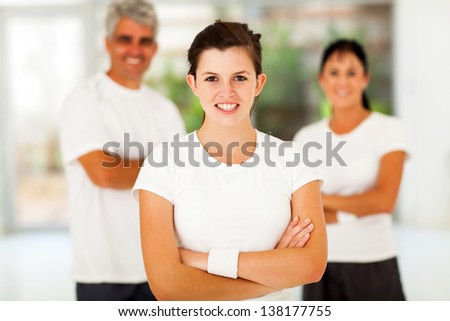 smiling active teenage girl arms folded standing in front of parents - stock photo