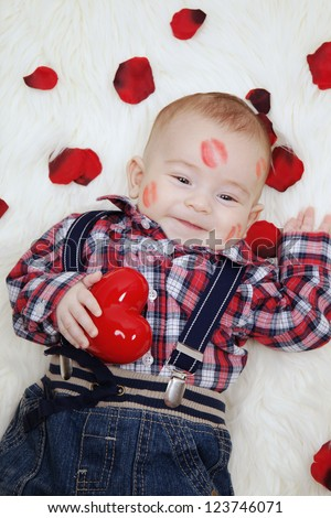 Smiling adorable baby boy with lipstick on his face holding valentines heart - stock photo