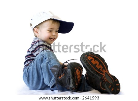 Smiling adorable baby in blue jeans and big shoes - stock photo
