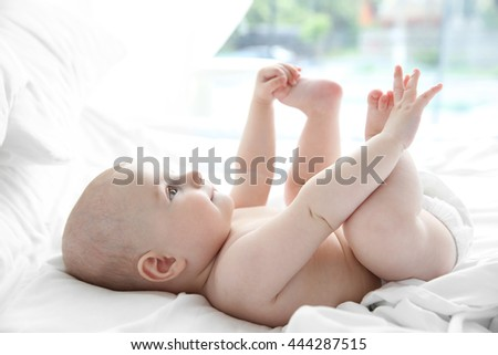 Smiling adorable baby on white bed