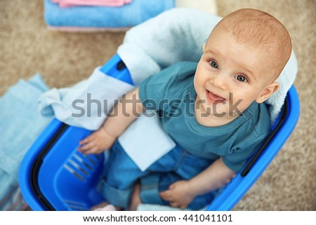 Smiling adorable baby with clothes in plastic basket - stock photo