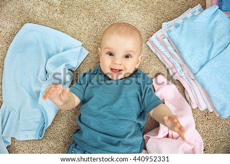 Smiling adorable baby with different clothes on the floor - stock photo