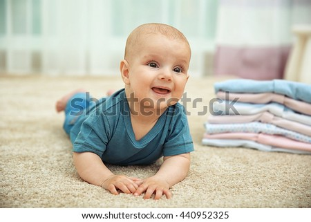Smiling adorable baby with pile of clothes on the floor - stock photo