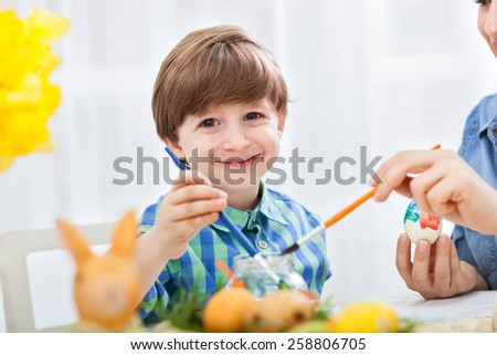 Smiling adorable child boy painting easter egg at home - stock photo