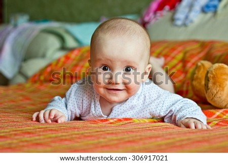 Smiling adorable little boy portrait. Lying on bed and looking at lens - stock photo
