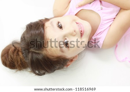 Smiling adorable little girl lying down, looking straight into the camera with focus on her face - stock photo