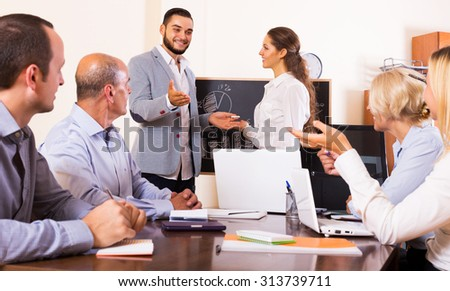 Smiling adult business people during conference call indoors