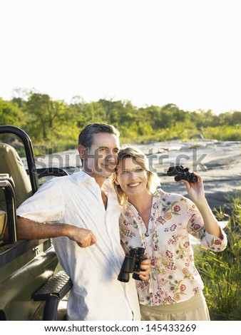 Smiling adult couple standing by jeep with binoculars  - stock photo