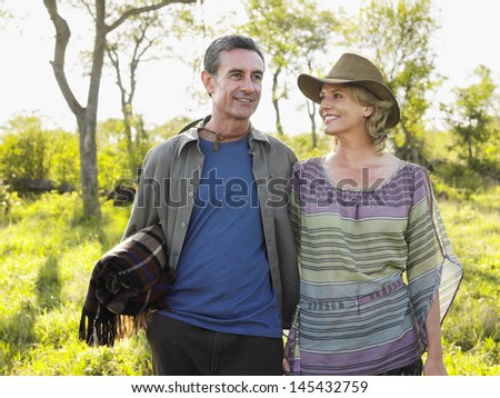 Smiling adult couple with man carrying blanket on meadow - stock photo