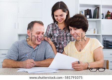 Smiling adult daughter helping with documents to her mature parents at a home. Focus on both mature persons