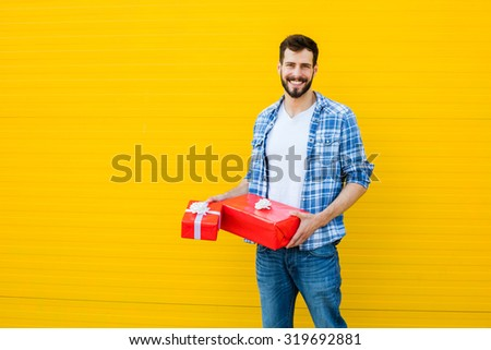 smiling adult man casual dressed with beard having red present in hand on yellow background, with text space - stock photo