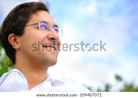 Smiling adult man looking to the sky - stock photo