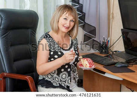 Smiling adult woman eating cake at desk in her apartment. Break during work on computer